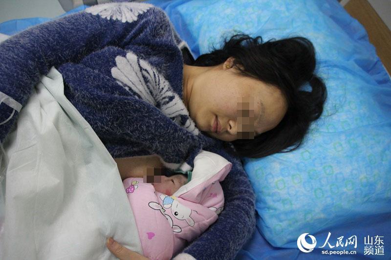 孩子躺在妈妈怀里贪婪地允吸母乳。(摄影 宋翠
