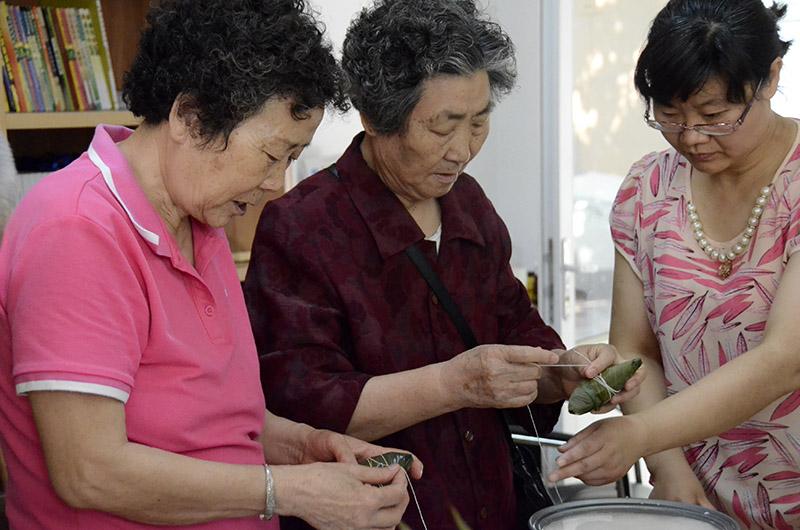 老奶奶们自发帮助居委会一起包粽子送给环卫工人们.(摄影:陈心同)