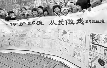 """三年级三班的学生正在展示自己手绘的宣传""""低碳""""手抄报.当高清图片"""