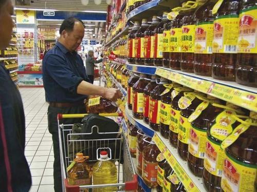 市民于广勤手推购物车里装了四桶食用油