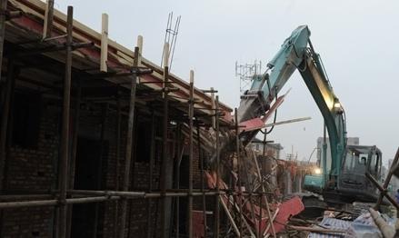 拆迁机开始对水天福苑小区西侧的违规建